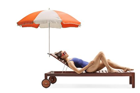 Full length profile shot of a young attractive woman in a swimsuit lying on a sunbed under umbrella isolated on white background