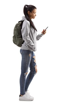 Full length profile shot of a young female with a hoodie and ripped jeans holding a mobile phone isolated on white background Reklamní fotografie