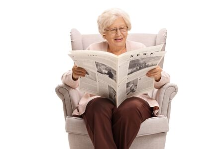 Senior lady sitting in an armchair and reading a newspaper isolated on white background 写真素材 - 129384688