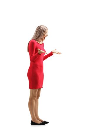 Full length shot of a surprised young woman in a red dress gesturing and screaming isolated on white background