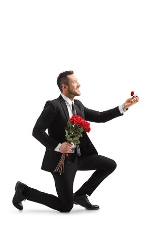 Young elegant man in a suit kneeling and holding roses and an engagement ring isolated on white background