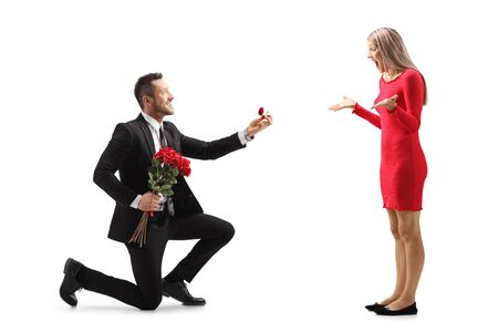 Young man kneeling with roses and an engagement ring and proposing to a surprised young woman isolated on white background