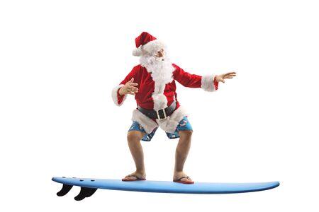 Disparo de longitud completa de Santa Claus en pantalones cortos de natación en una tabla de surf aislado sobre fondo blanco.