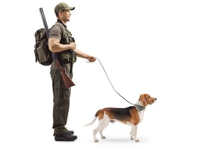 Full length profile shot of a hunter standing with a rifle and a beagle dog on a leash isolated on white background