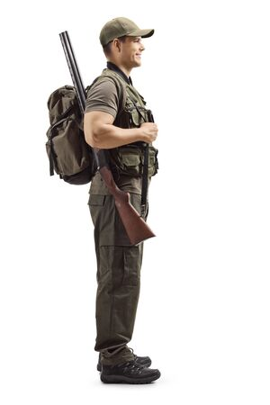 Full length profile shot of a hunter standing with a rifle isolated on white background