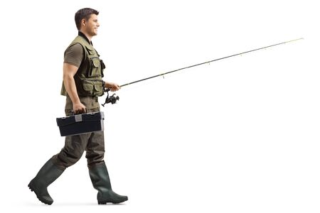 Full length profile shot of a fisherman with a fishing rod walking isolated on white background 스톡 콘텐츠