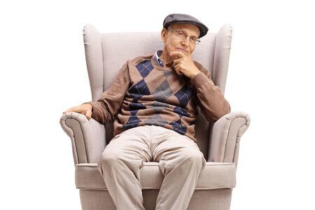 Elderly man sitting in an armchair and thinking isolated on white background Фото со стока