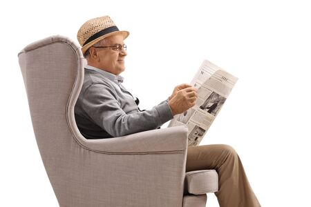 Cheerful mature man sitting in an armchair and reading a newspaper isolated on white background 写真素材