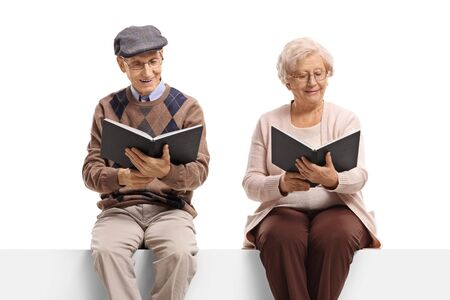 Elderly man and woman seated on a panel reading books isolated on white background Stok Fotoğraf
