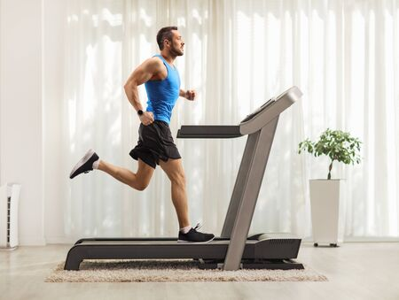 Full length profile shot of a young man running on a treadmill at home Stockfoto