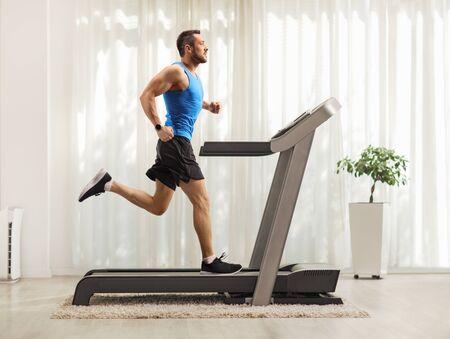 Pełne ujęcie profilowe młodego mężczyzny biegnącego na bieżni w domu