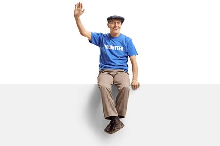 Full length shot of an elderly male volunteer sitting on panel and waving isolated on white background