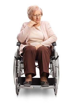 Thoughtful elderly woman sitting in a wheelchair isolated on white
