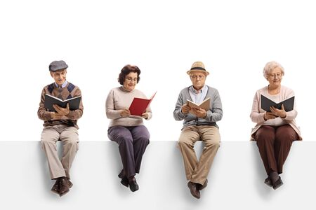 Group of elderly people sitting on a white panel reading books isolated on white