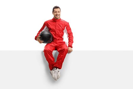 Full length portrait of a racer in a red uniform sitting on a panel holding a helmet and smiling isolated on white