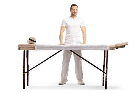 Full length portrait of a male masseur standing behind a professional massage bed isolated on white Фото со стока
