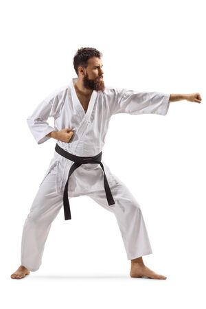 Full length shot of a bearded man in kimono practicing karate isolated on white Imagens