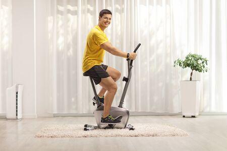 Giovane che si esercita su una cyclette a casa