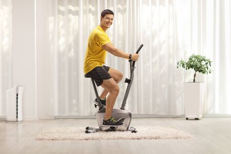 Young man exercising on a stationary bike at home