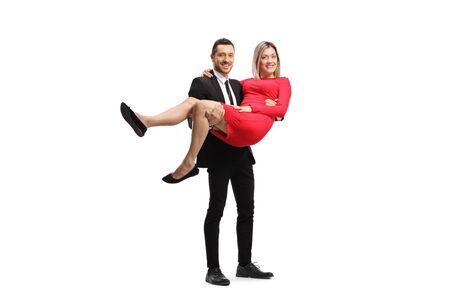 Homme élégant portant une femme vêtue d'une robe rouge dans ses bras isolé sur blanc