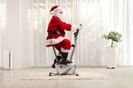 Santa Claus exercising on a stationary bicycle in a luxury home