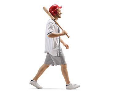 Full length profile shot of a guy walking with a baseball bat and a helmet isolated on white Stock Photo