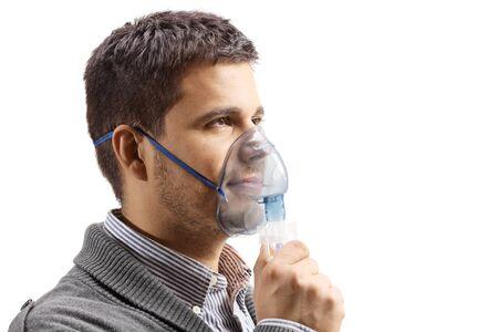 Hombre joven con una máscara de inhalación aislado en blanco