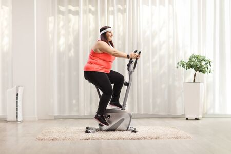Overweight woman exercising on a stationary bike at home