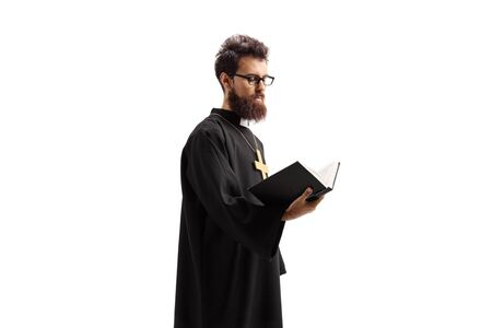 Priest standing and reading the Bible isolated on white Фото со стока