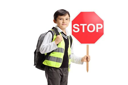 Schoolboy wearing a safety vest and holding a stop sign isolated on white