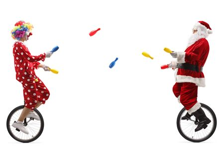 Disparo de longitud completa de un payaso y santa claus en monociclo y haciendo malabares aislado en blanco