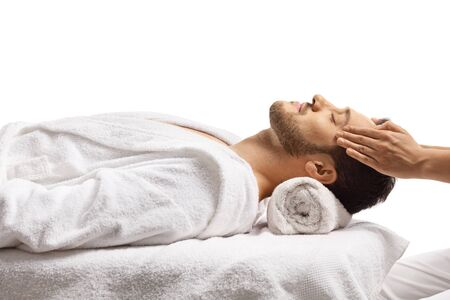 Man at a spa center enjoying a head massage isolated on white