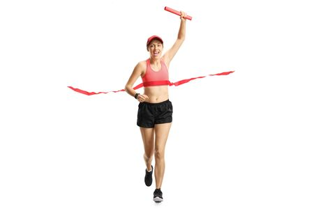 Full length portrait of a young woman carrying a red baton and finishing a relay race isolated on white Stock fotó