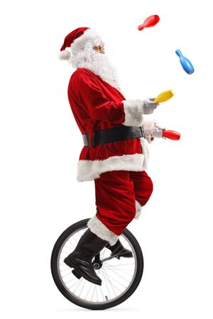 Full length shot of santa claus riding a unicycle and juggling with clubs isolated on white Фото со стока