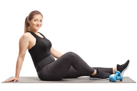 Full length shot of a young woman sitting on an exercising mat with dumbbells isolated on white background