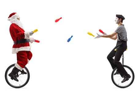 Full length shot of santa claus and a mime on unicycles juggling with clubs isolated on white background Stock Photo