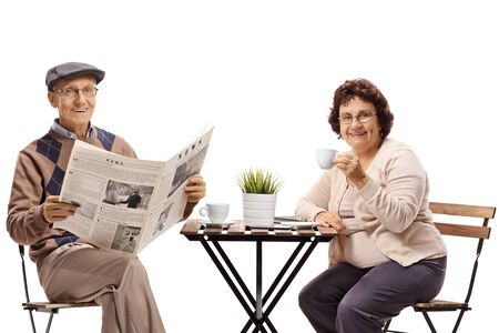 Senior man and woman having coffee and reading newspaper isolated on white background 写真素材