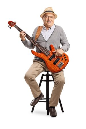 Full length portrait of a senior gentleman sitting on a high chair and holding a bass guitar isolated on white background