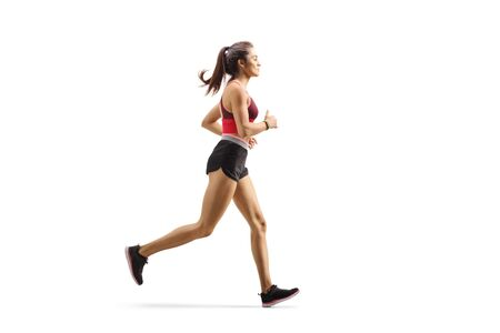Full length profile shot of a female athlete jogging isolated on white background