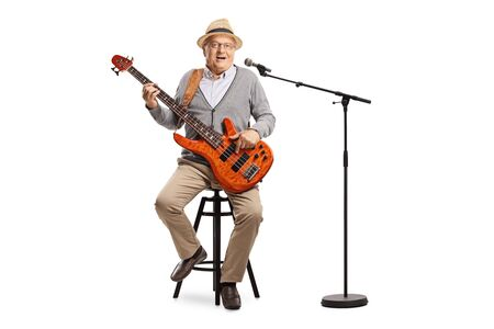 Full length portrait of an elderly bass guitarist sitting on a high chair with microphone isolated on white background