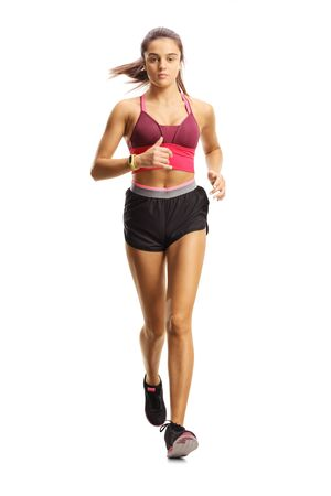 Full length portrait of a young female athlete running towards camera isolated on white background Banco de Imagens
