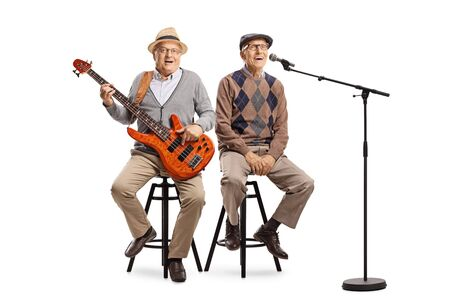 Full length portrait of two senior men sitting with an electric guitar and a microphone isolated on white background Stock Photo
