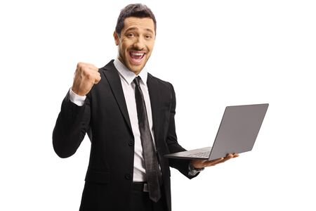 Young businessman gesturing yeah and holding a laptop computer isolated on white background