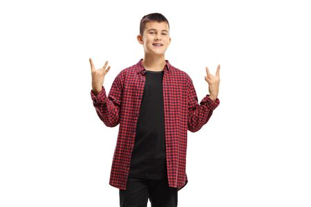 Cheerful teenage boy making a hand gesture sign of the horns isolated on white background