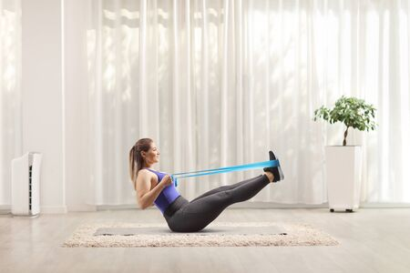 Full length profile shot of a young woman exercising with an elastic band on the floor