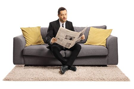 Full length portrait of a young businessman sitting on a sofa and reading a newspaper isolated on white background 写真素材