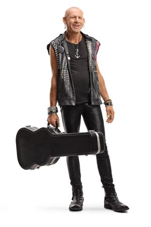 Full length portrait of a rock musician in leather outfit with a guitar case smiling at the camera isolated on white background
