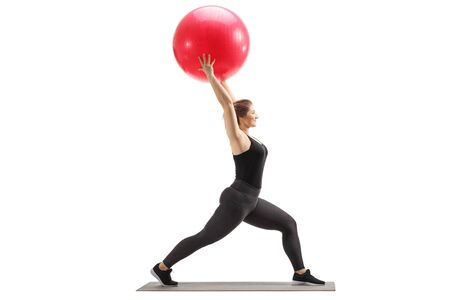 Full length profile shot of a young woman lifting a fitness ball up isolated on white 스톡 콘텐츠