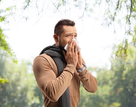 Man sneezing and suffering from a hay fever allergy outdoors