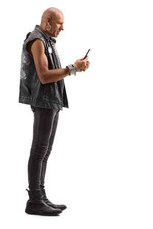 Full length profile shot of a punk in leather clothing standing and typing on a mobile phone isolated on white